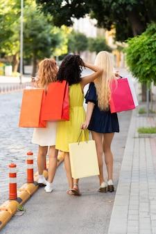 Vista frontale delle ragazze con le borse della spesa