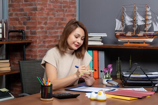 Vista frontale felice donna d'affari che prende appunti seduta alla scrivania in ufficio
