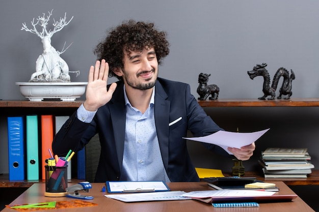Front view glad businessman hailing someone in his office