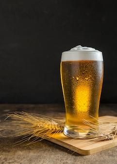 Vista frontale del bicchiere di birra con il grano