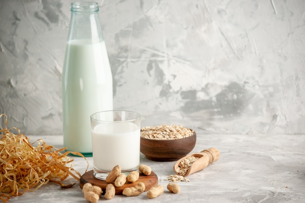 Front view of glass bottle and cup filled with milk on wooden tray and dry fruits spoon oats in brown pot on the left side on white table on ice background