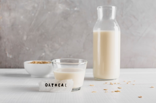 Front view glass and bottle of milk woth oatmeal