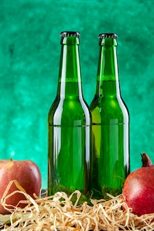Front view glass bottles with pomegranates on green desk drink lemonade color photo