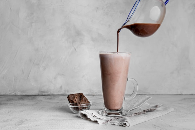 Front view of glass of chocolate milk with cloth