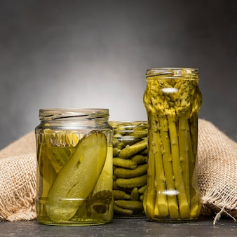 Front view of glass jars with pickled asparagus and cucumbers