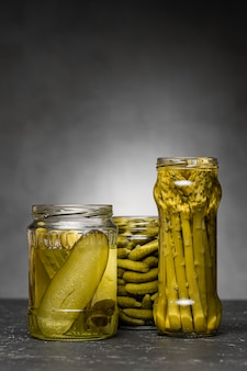 Front view of glass jars with pickled cucumbers and asparagus