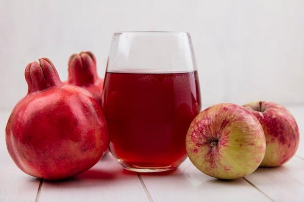 Стакан гранатового сока с яблоками и гранатами на белой стене, вид спереди