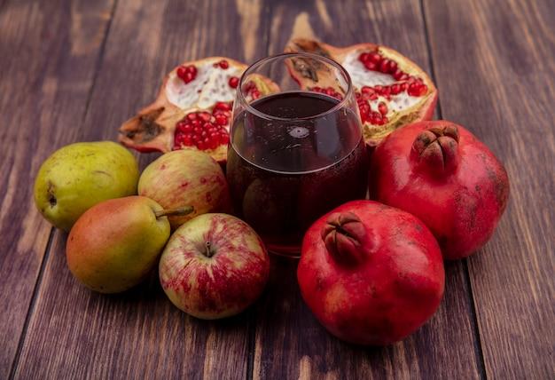 Стакан гранатового сока с гранатами, яблоками и грушами на деревянной стене, вид спереди