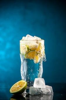青い写真のシャンパン水カクテル レモネードにレモン スライスと氷の入ったソーダの正面ガラス