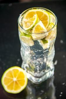 暗い写真のシャンパン ウォーター カクテル ドリンク レモネードにレモン スライスとソーダの正面ガラス