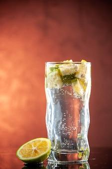 Стакан содовой с дольками лимона, вид спереди, на светло-розовом фото, шампанское, вода, коктейль, напиток, лимонад