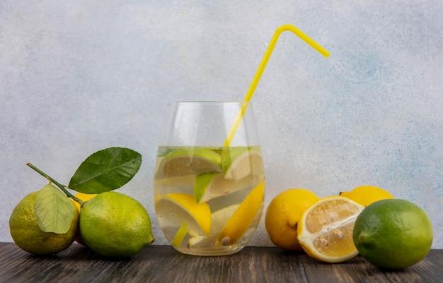 ライムと黄色のわらとレモンスライスと水の正面図ガラス