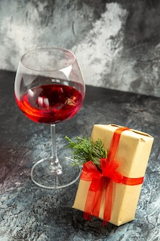 Вид спереди бокал вина в подарок на темном фоне