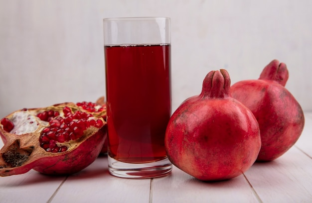 Front view glass of pomegranate juice with pomegranates on white wall