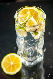 Front view glass of soda with lemon slices on a dark photo champagne water cocktail drink lemonade