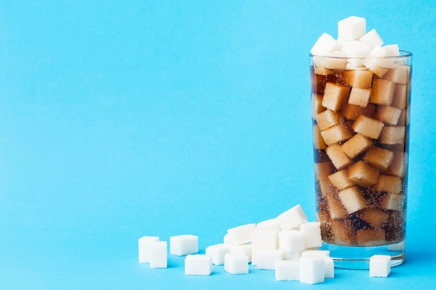 Front view of glass of soft drink with sugar cubes and copy space