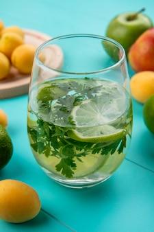 Vista frontale del bicchiere d'acqua con verdure e calce su una superficie blu
