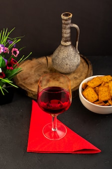 A front view glass of wine along with flower and crisps inside plate on dark desk