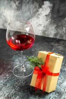 Vista frontale del regalo di un bicchiere di vino su sfondo scuro