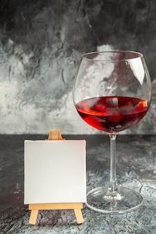 Vista frontale bicchiere di vino tela bianca su cavalletto in legno su oscurità