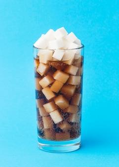 Vista frontale del vetro con bibita e zollette di zucchero