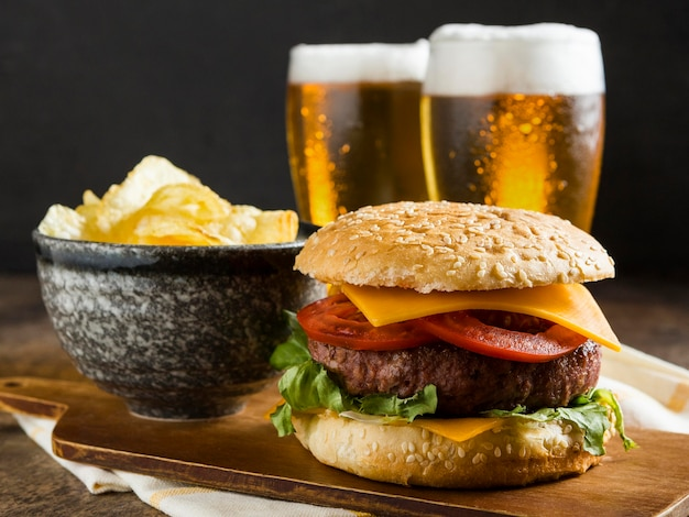 Front view of glasses of beer with cheeseburger and chips