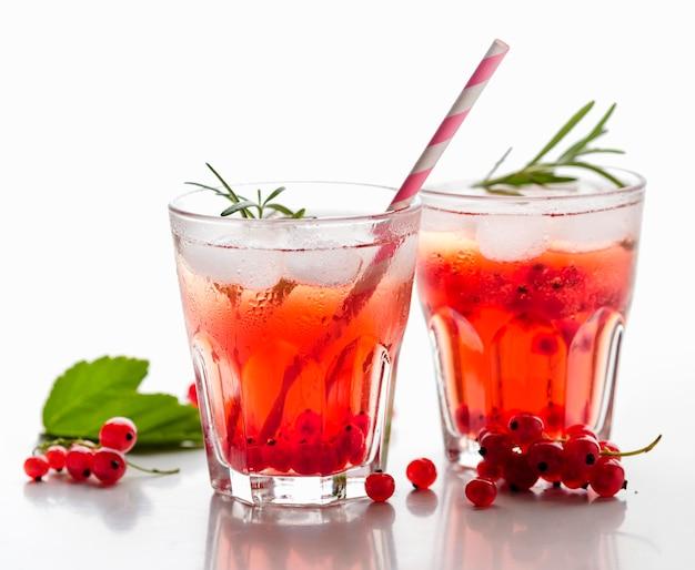 Bicchieri di vista frontale di vodka al mirtillo rosso con ghiaccio