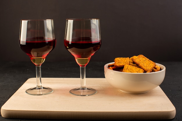 A front view glasses of wine along with crisps inside plate on wooden desk and dark