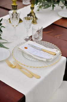 Front view of glassware and cutlery served on the wooden table