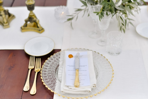 Front view of glassware and golden cutlery served on the wooden table and printed guest nameplate and white fabric serviettes