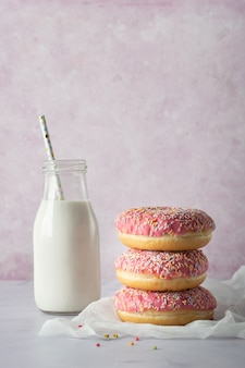 Front view of glazed doughnuts with sprinkled and milk bottle