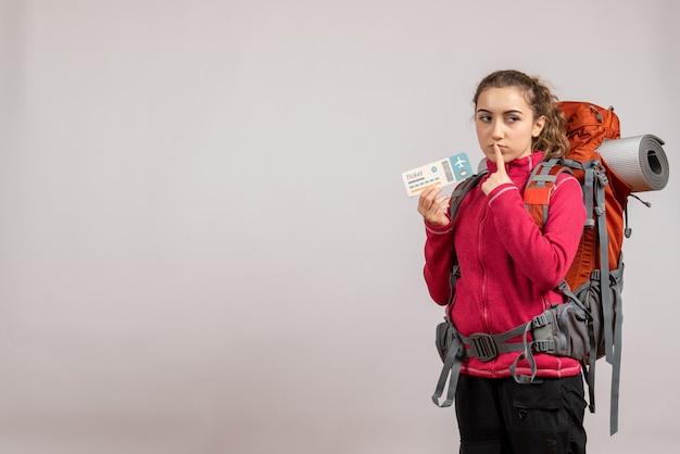 Vista frontale del giovane viaggiatore glumpsy con il grande zaino che sostiene il biglietto di viaggio