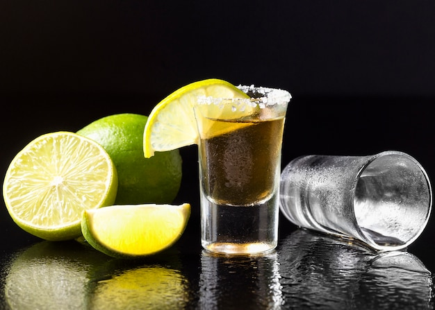Front view gold tequila shot with lime and salt