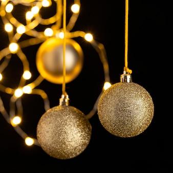 Vista frontale dei globi dorati di natale con le luci