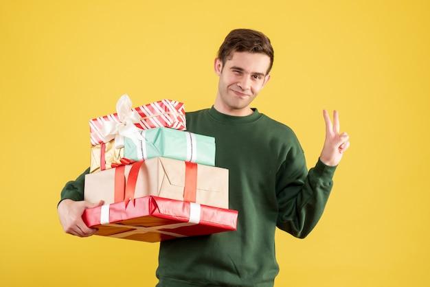 Красивый мужчина с зеленым свитером делает знак победы, стоя на желтом, вид спереди
