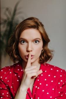 Vista frontale della donna splendida che mostra il segno di silenzio. tiro al coperto del modello femminile riccio in pigiama rosso.