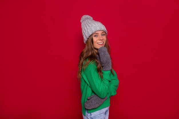 Vista frontale della splendida giovane donna in cappello lavorato a maglia e maglione verde