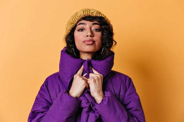 Vista frontale della splendida giovane donna in cappello lavorato a maglia