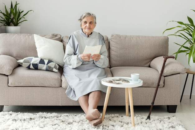 Вид спереди бабушка проверяет старые фотографии