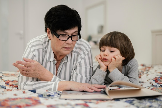Front view of grandmother and grandson at home reading