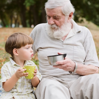 Front view grandpa and grandson drinking tea