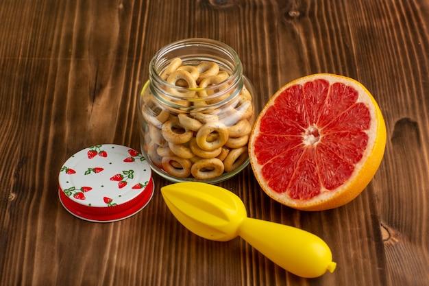 Вид спереди грейпфрут и крекеры на коричневом столе