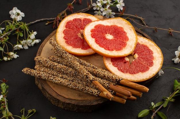 Вид спереди грейпфрутовые леденцы нарезанные цитрусовые спелые на коричневом столе на темноте