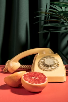 Front view grapefruit next to vintage telephone