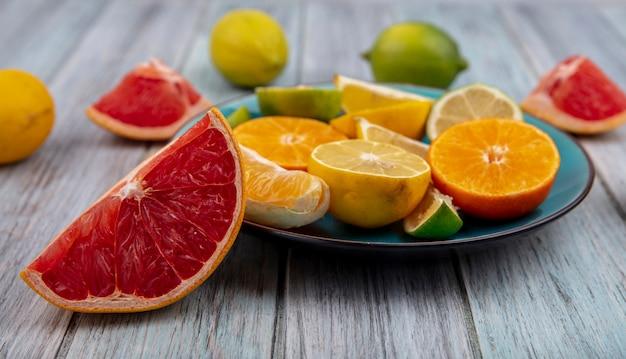 회색 배경에 접시에 레몬 라임과 오렌지 웨지와 전면보기 자몽 웨지
