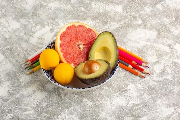 Вид спереди грейпфруты и авокадо внутри тарелки с карандашами на белой поверхности