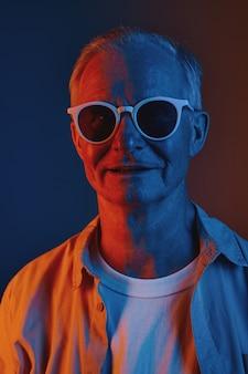 赤と青、コピースペースでサングラスをかけている年配の男性の正面図のグラフィックカラーの肖像画