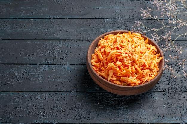 Insalata di carote grattugiate vista frontale all'interno del piatto sul colore blu scuro dell'insalata di salute della scrivania rustica verdure mature dietetiche