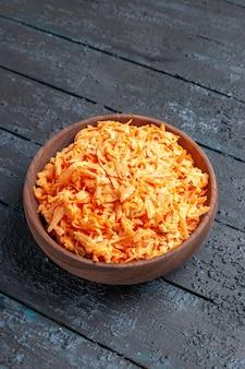 Insalata di carote grattugiate vista frontale all'interno del piatto su insalata di colore rustico blu scuro dieta salute vegetale