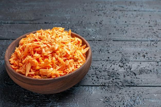 Insalata di carote grattugiate vista frontale all'interno del piatto sull'insalata da scrivania rustica blu scuro colore maturo dieta salute vegetale
